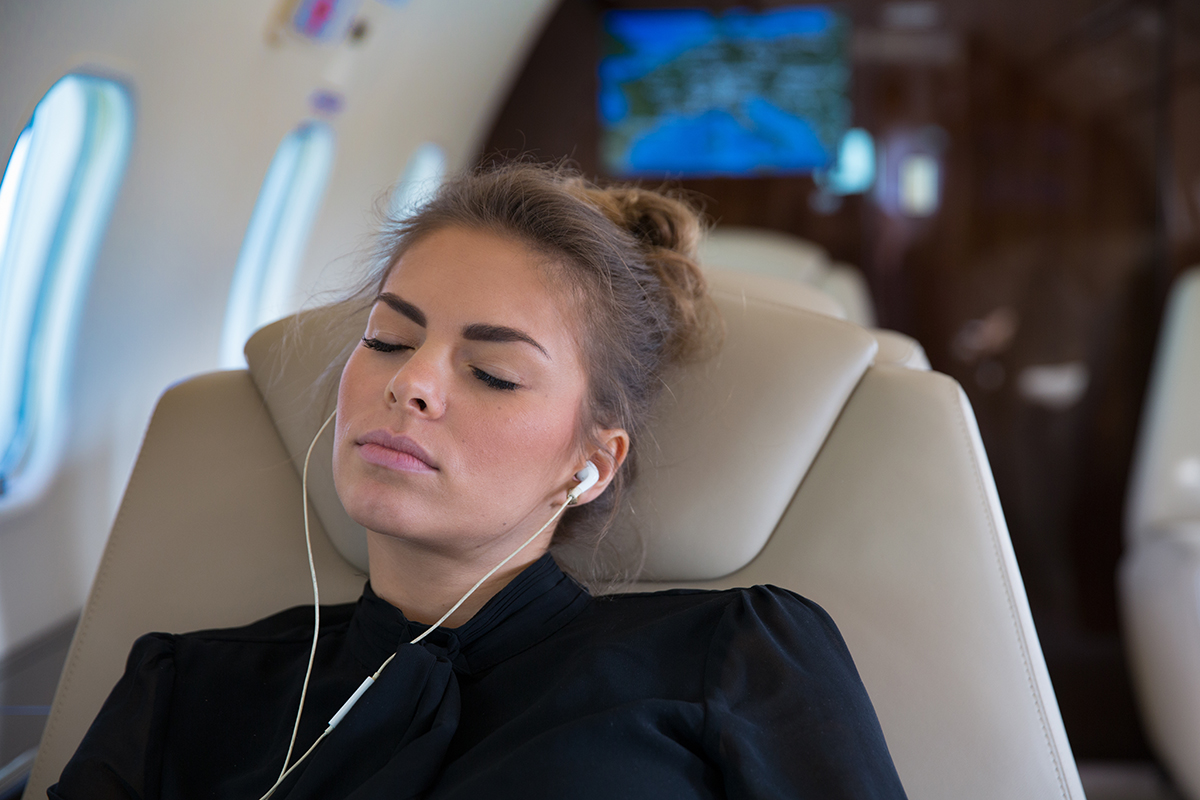 Woman listening to music on a private jet charter to Los Angeles