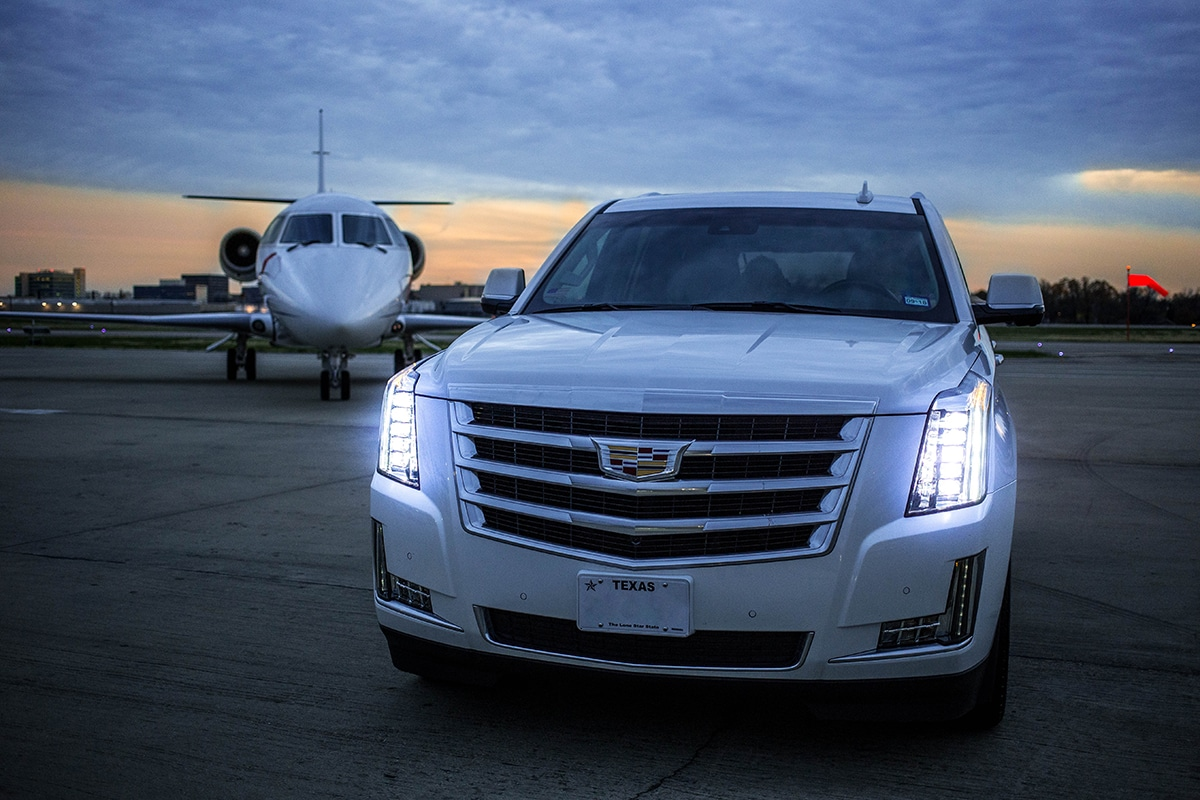 Cadillac Escalade Parked next to a private jet on a runway